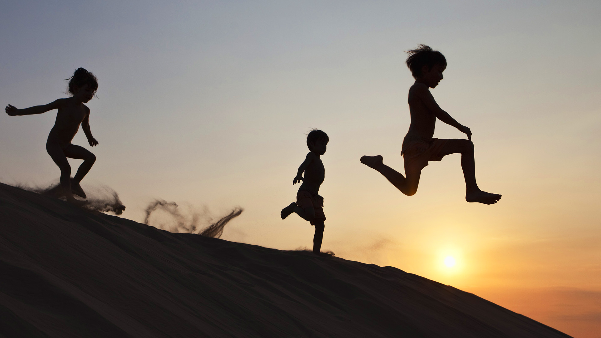 Children running down a sand dune --- Image by © Sven Hagolani/Corbis